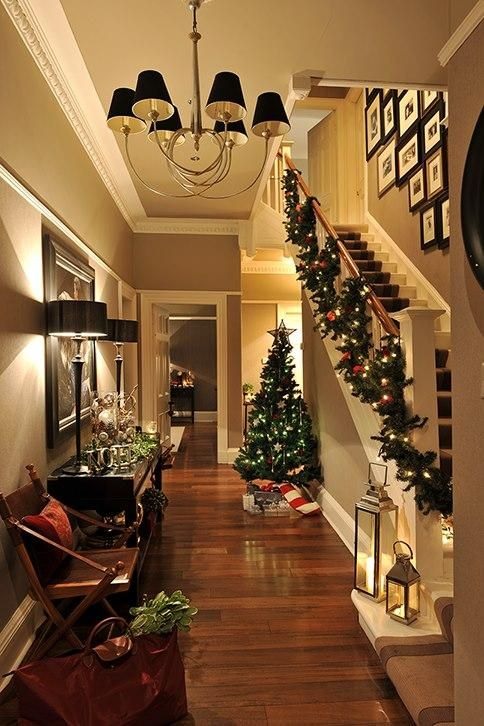 Treat your hallway as a room in its own right. It is the first impression visitors will receive when they enter. Candles and a stairway garland look festive, while the Christmas tree draws your eye further inside.    Source: @Houseologists
