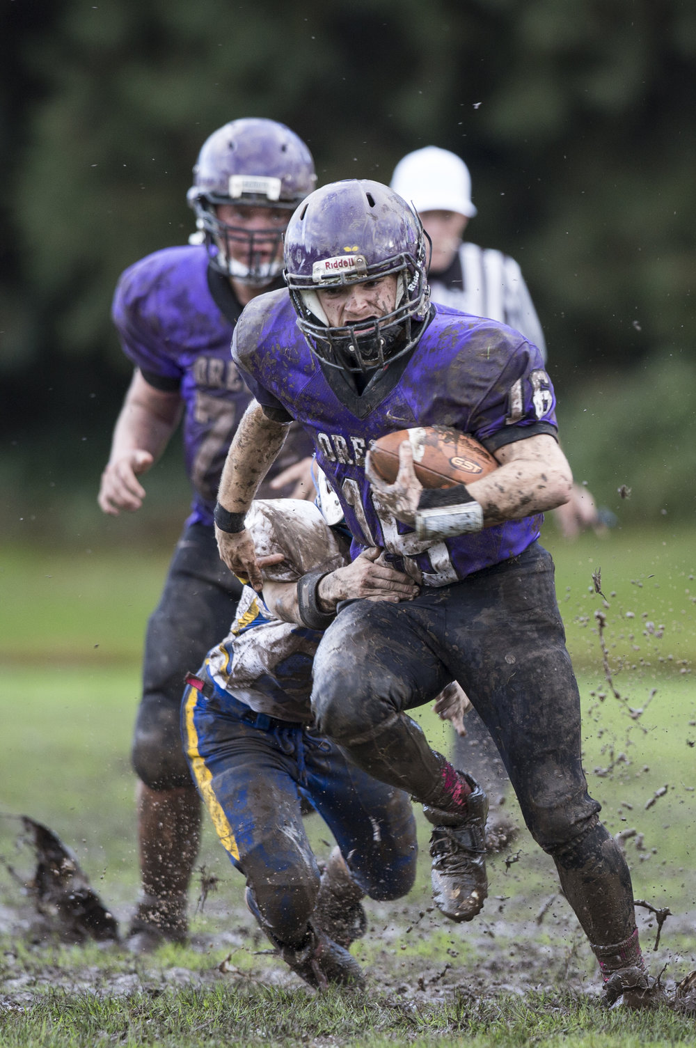 Oregon School for the Deaf junior Hunter Lively (#16) powers through the muddy field. Oregon School for the Deaf defeated Jewell 48-19.