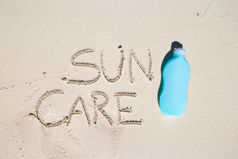 Suncare written on tropical white sand and suncream