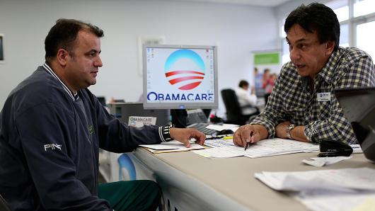 Getty Images A customer speaks with an insurance agent as he signs up for Affordable Care Act in Miami.
