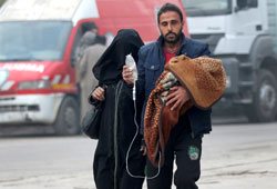 A man carries a child with an IV drip as he flees deeper into the remaining rebel-held areas of Aleppo, Syria. REUTERS/Abdalrhman Ismail