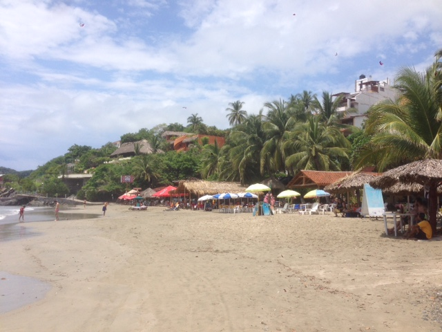 A view of the beach from the surf. The umbrellas and covered pavilions are restaurants similar to where C.and his friend work.