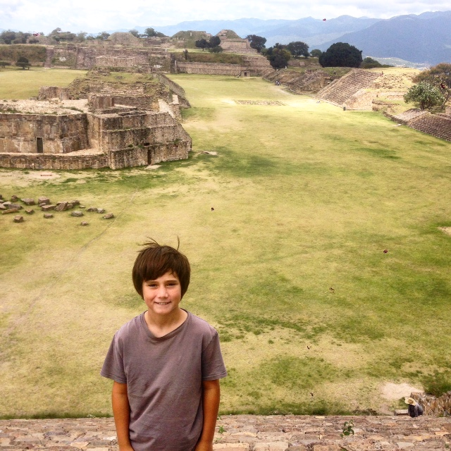 J standing on top of the South Platform with a view behind him of the Grand Plaza at Monte Alban.