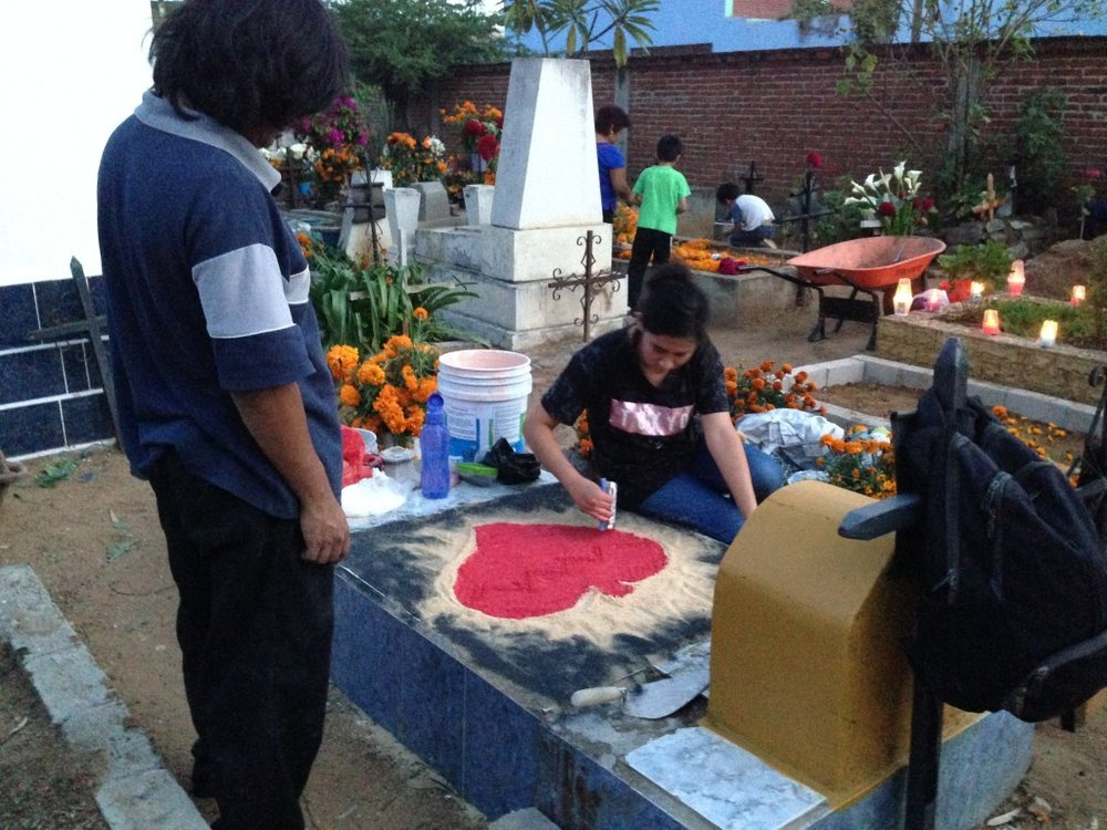 Families spend hours cleaning and decorating graves, to honor and remember the dead.  Here a woman decorates with colored sand.