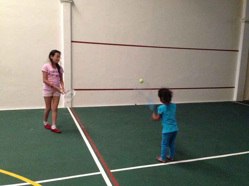 The girls learn the finer points of tennis.