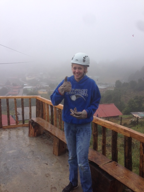 Zoe gives a thumbs up after surviving a zip line through the fog and rain.