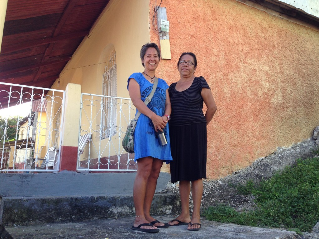 R standing in front of the house where she lived with the sister of the matriarch. The matriarch recently passed away.