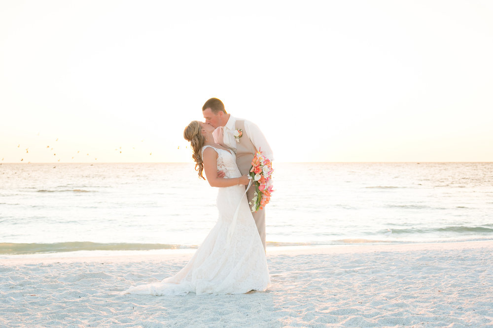 bride and groom photo on the beach kissing at Guy Harvey Resort, Florida