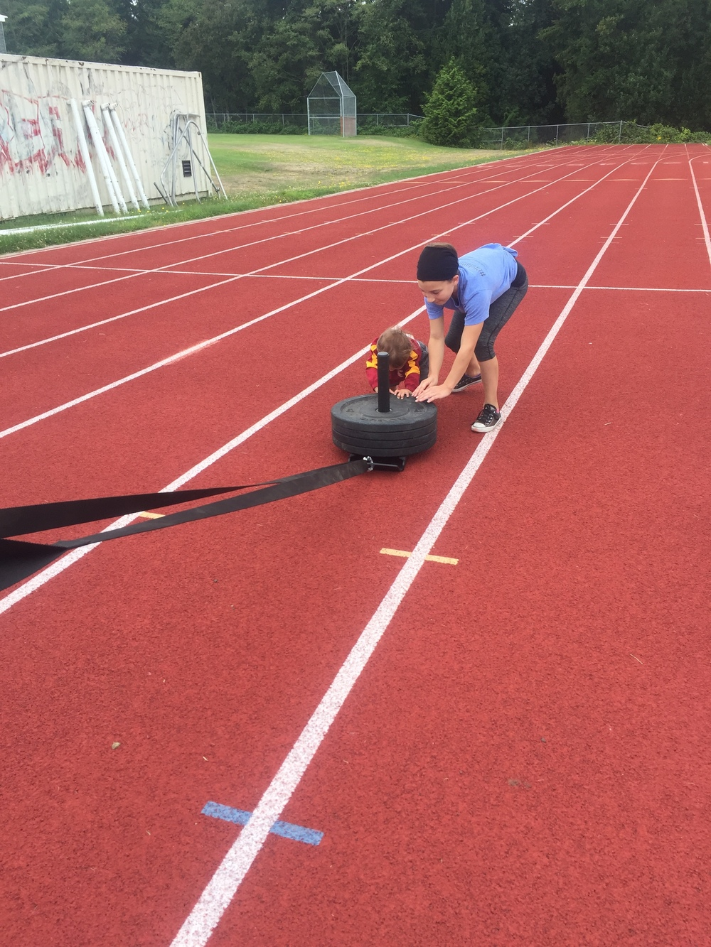 Junior Athlete (Brodie) working with Walker on sled pushes on Track Day