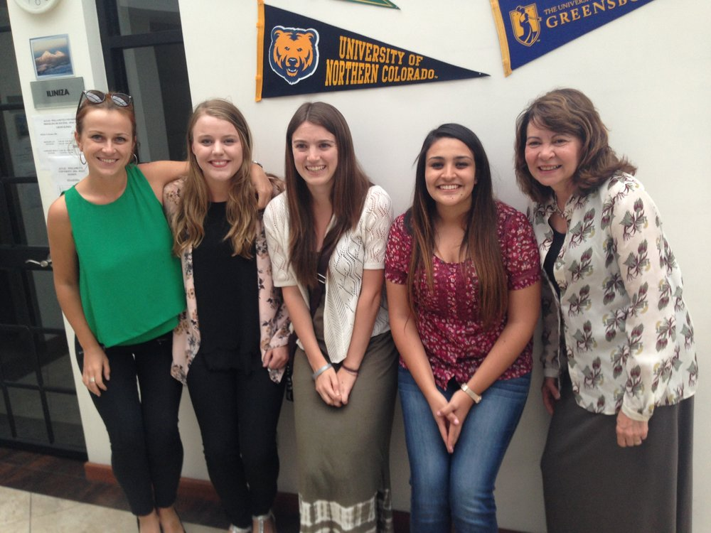 University of Northern Colorado Education students and faculty member pose with their school's pennant.