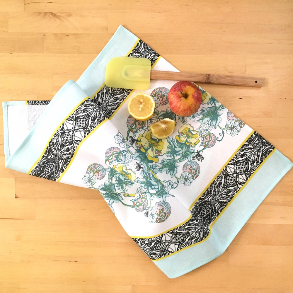 Janice Nelson made ethically in USA Celandine Tea Towel with yellow flowers on table