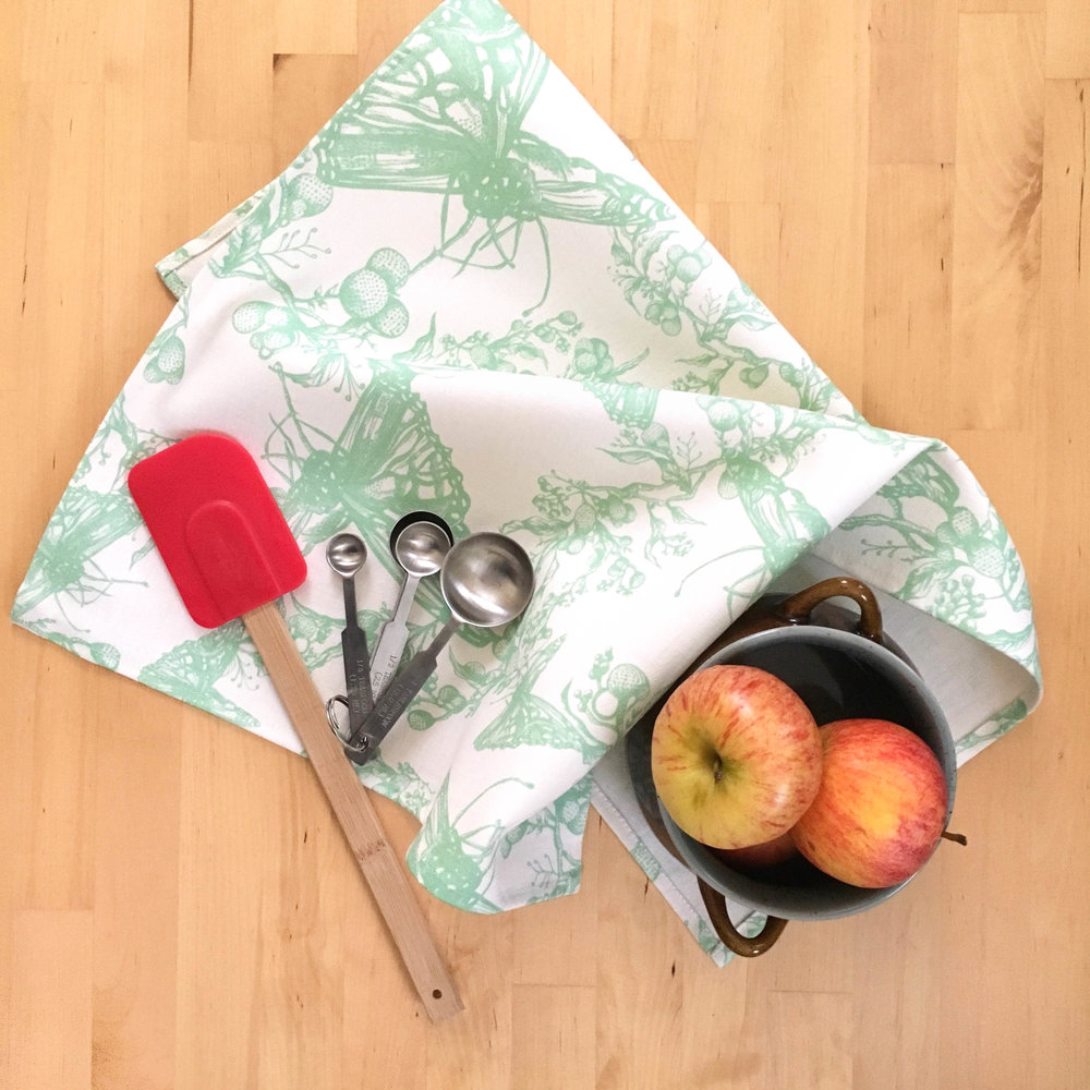 Cynthia Tea Towel with allover pale green butterfly pattern on table with fruit
