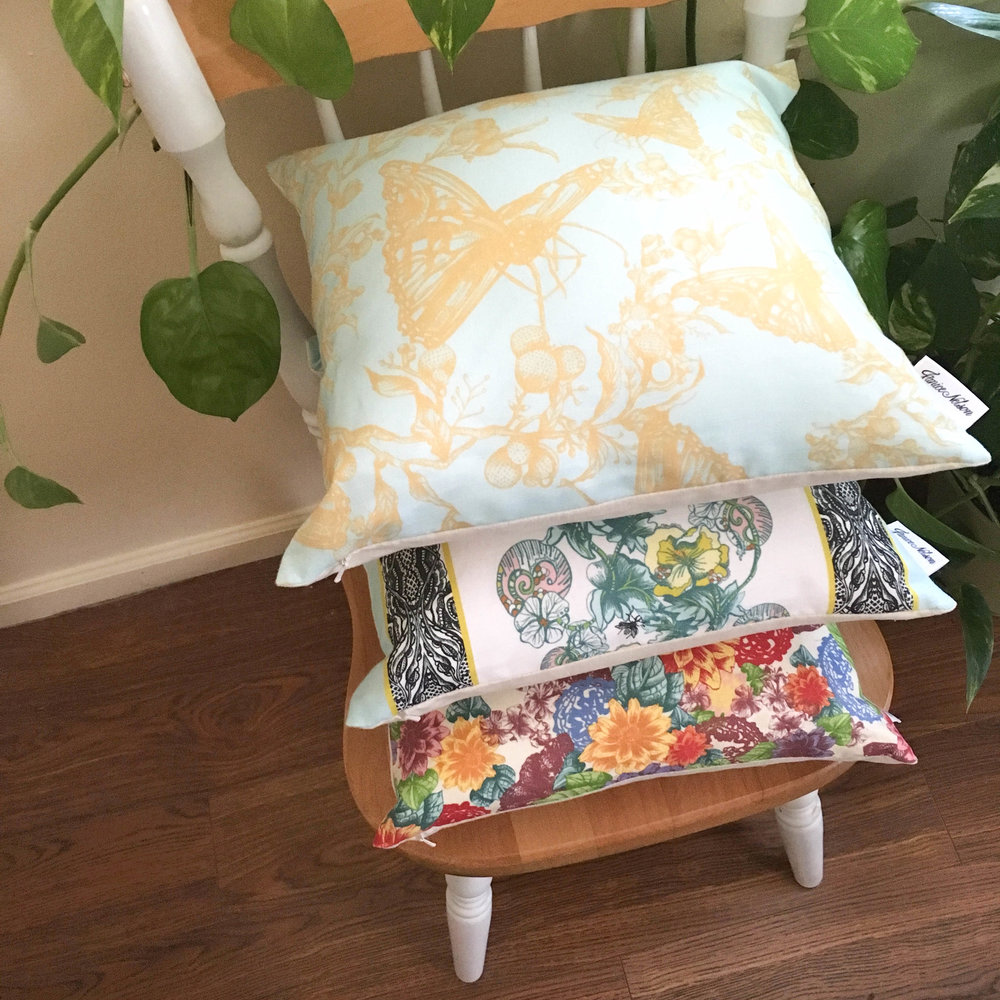 Three pillows stacked on wooden chair