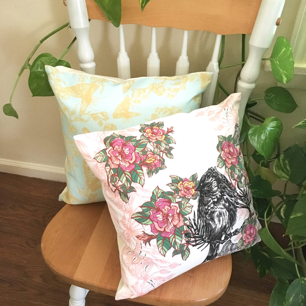 Acanthis Pillow with cheerful pink flowers and detailed bird illustration on a wooden chair next to Cynthia Pillow with golden butterflies