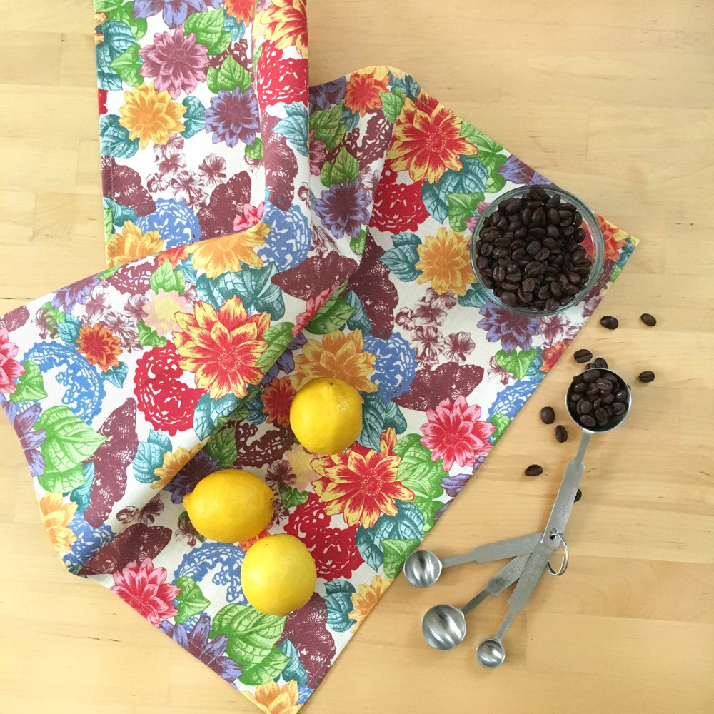 Bright and colorful Zale Tea Towel displayed on a table with coffee beans and lemons
