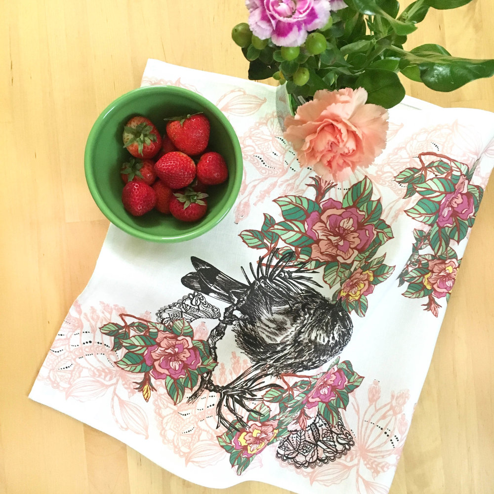 Acanthis Tea Towel on a table with a bowl of strawberries