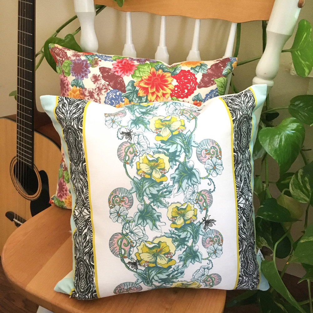 Ethically made Celandine pillow with meandering yellow flowers sits next to a colorful Zale pillow on a chair