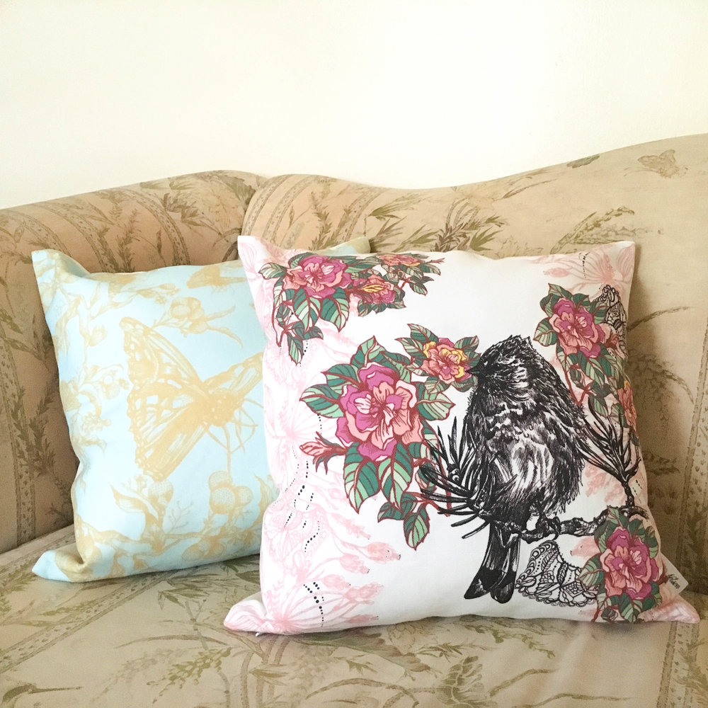 Acanthis pillow  and Cynthia pillow resting on a sofa.