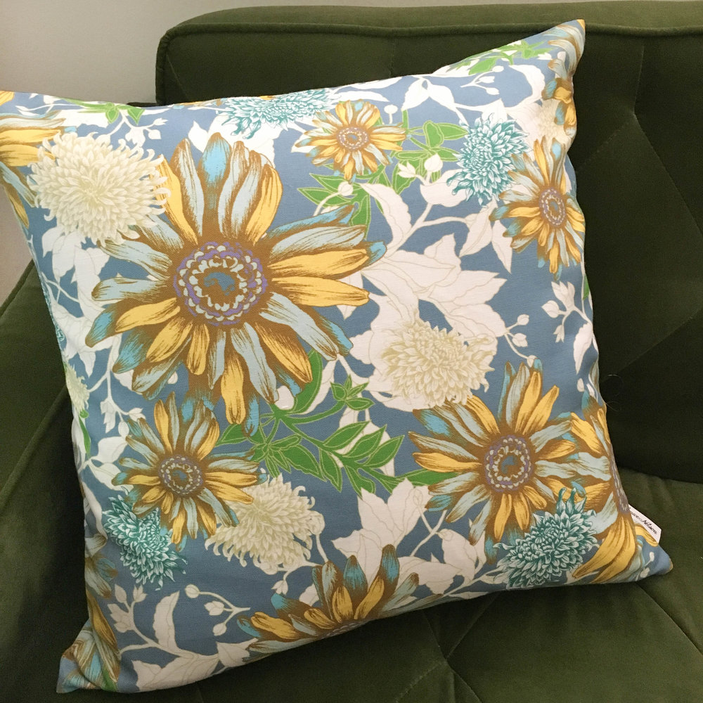 Luxurious 20x20 Gerbera pillow has warm golden yellow daisies and meandering leaves with pops of teal, turquoise, cream, and blue