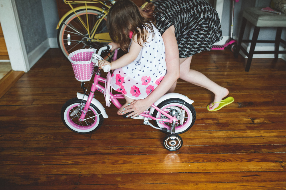 Mom helping daughter learn to ride bike.
