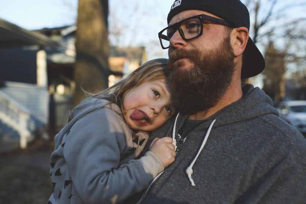 Little boy resting on dads shoulder.