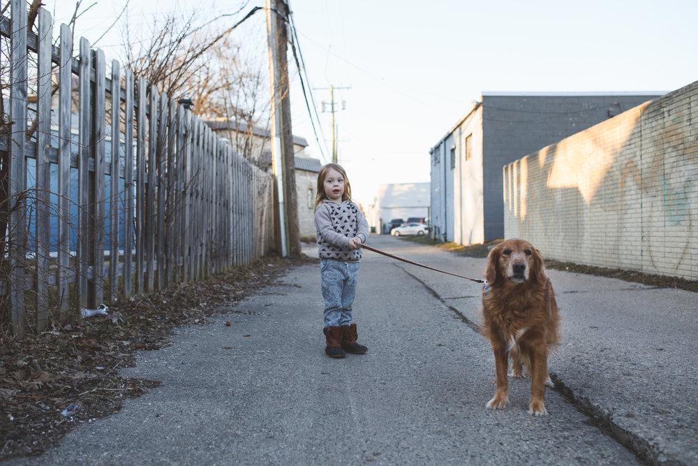 Little boy walking his dog.