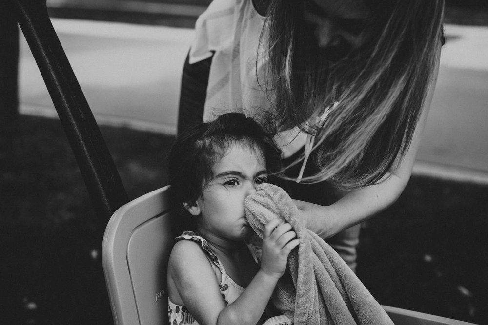 Mom wiping daughters nose with blanket.