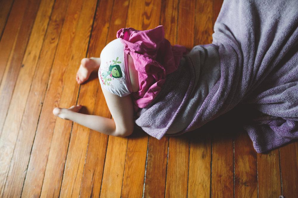 Little girl sticking head into blanket.