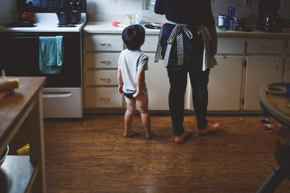 Kid picking underwear in kitchen.