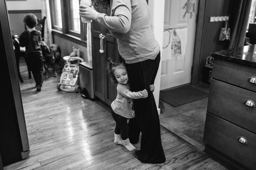 Toddler hugging moms leg while she walks.
