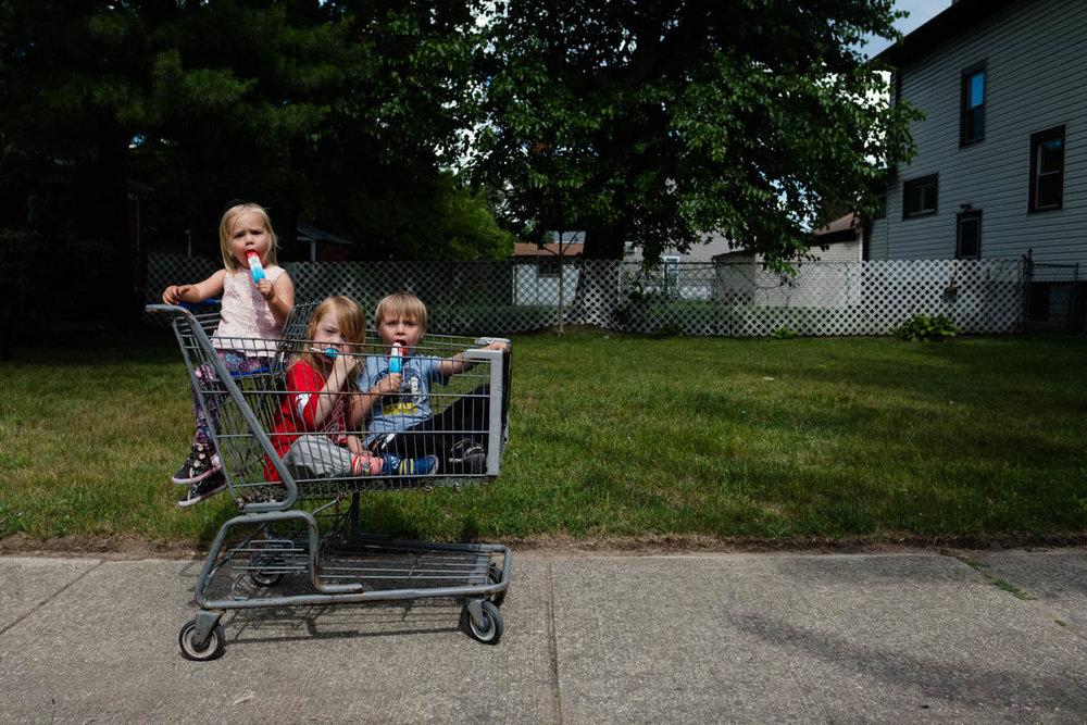 Kids in shopping cart eating ice cream.