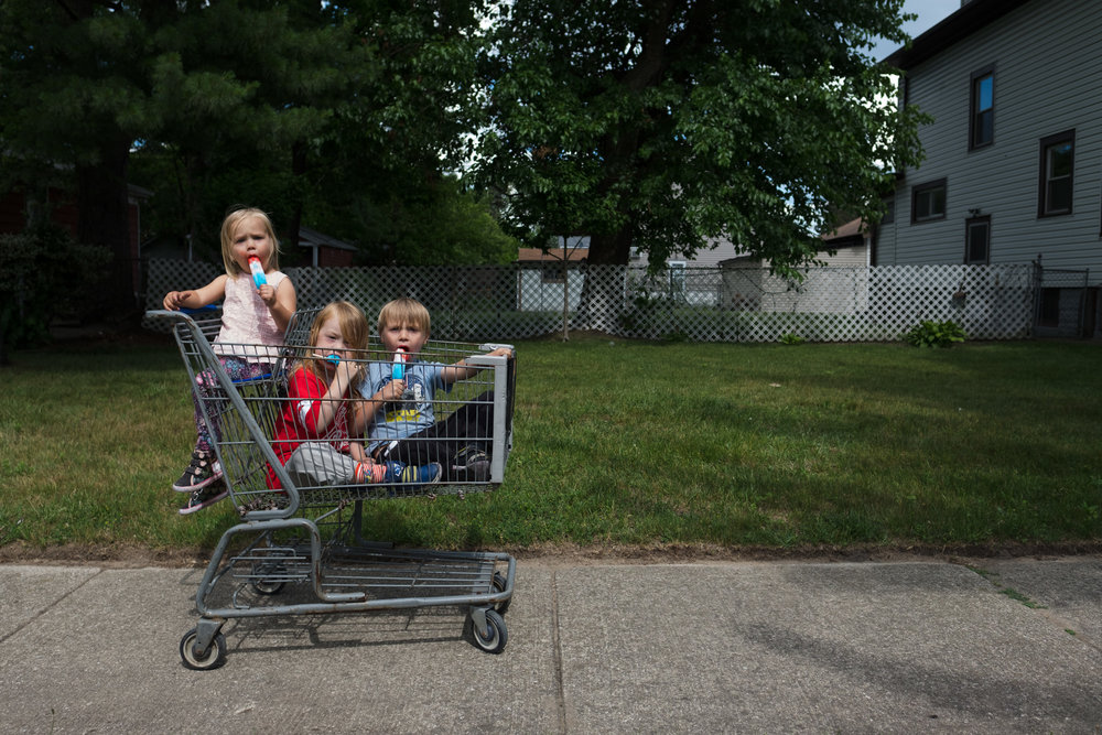 Kids eating popsicle in shopping cart.