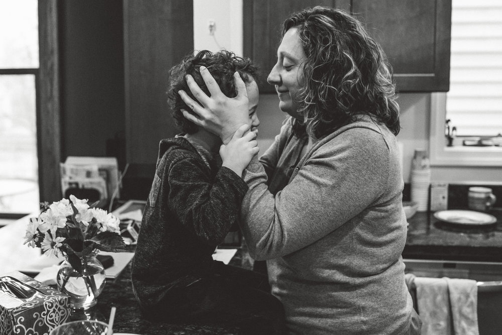 Mom kissing son's forehead.