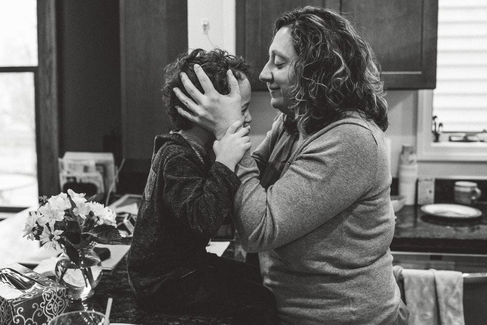 Mom kissing son's forehead.