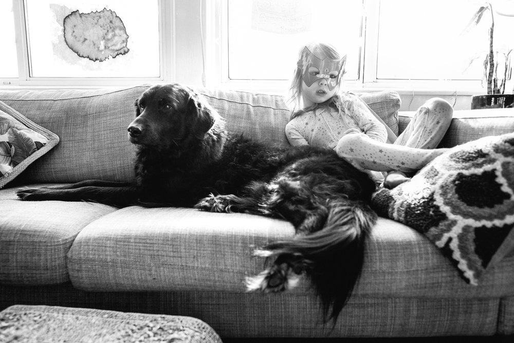 Kid sitting with dog on couch.