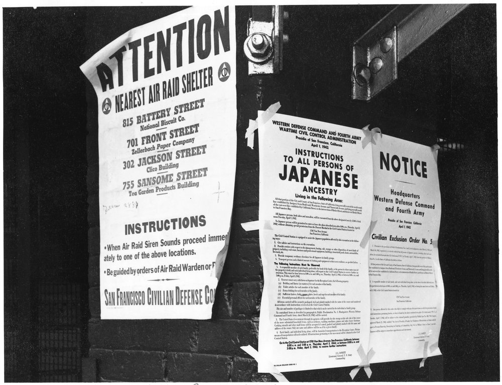 April 11, 1942 — San Francisco, California. On a brick wall beside air raid shelter poster, exclusion orders were posted at First and Front Streets directing removal of persons of Japanese ancestry from first San Francisco section to be affected by evacuation. The order was issued April 1, 1942, by Lieutenant General J.L. DeWitt, and directed evacuation from this section by noon on April 7, 1942.