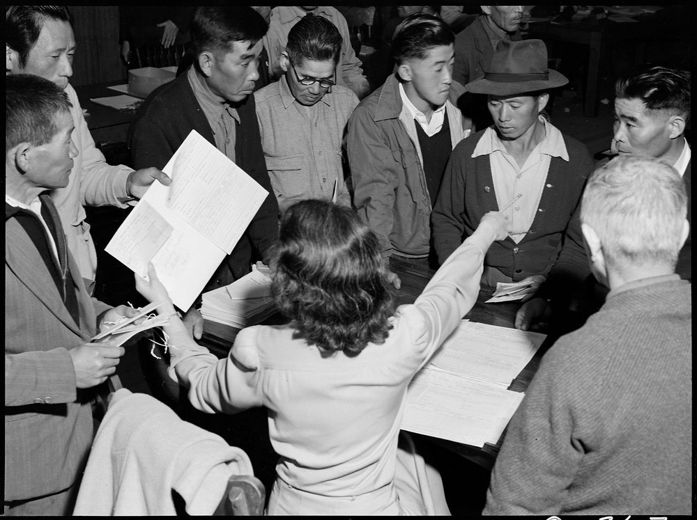 April 28, 1942 — Byron, California. These field laborers of Japanese ancestry at Wartime Civil Control Administration Control Station are receiving final instructions regarding their evacuation to an Assembly center in three days.