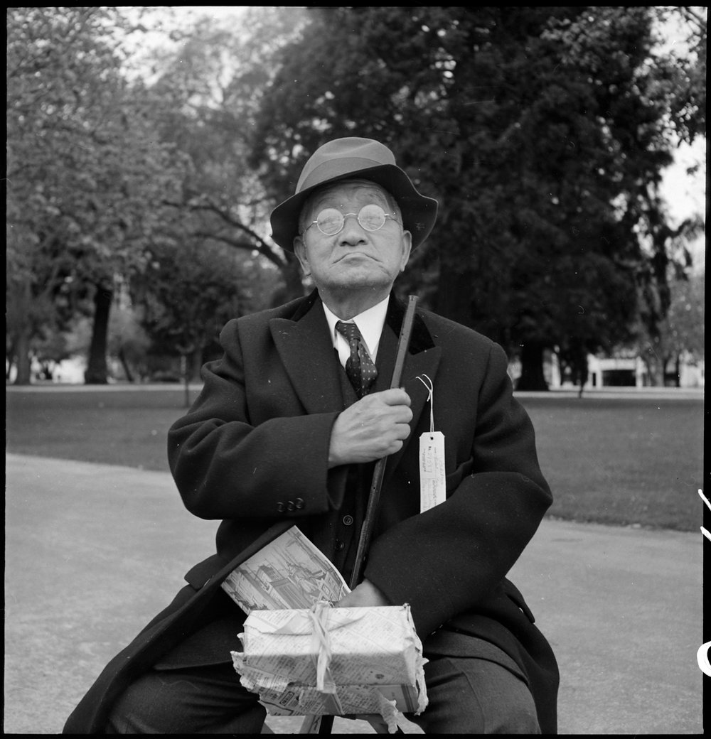 May 8, 1942 — Hayward, California. Grandfather of Japanese ancestry waiting at local park for the arrival of evacuation bus which will take him and other evacuees to the Tanforan Assembly center. He was engaged in the Cleaning and Dyeing business in Hayward for many years.