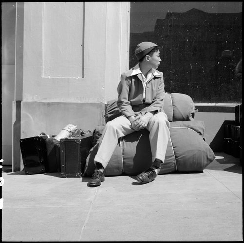 San Francisco, California. An early comer arrives with personal effects at 2020 Van Ness Avenue as part of the contingent of 664 residents of Japanese ancestry, first to be evacuated from San Francisco on April 6, 1942. Evacuees will be housed in War Relocation Authority centers for the duration.