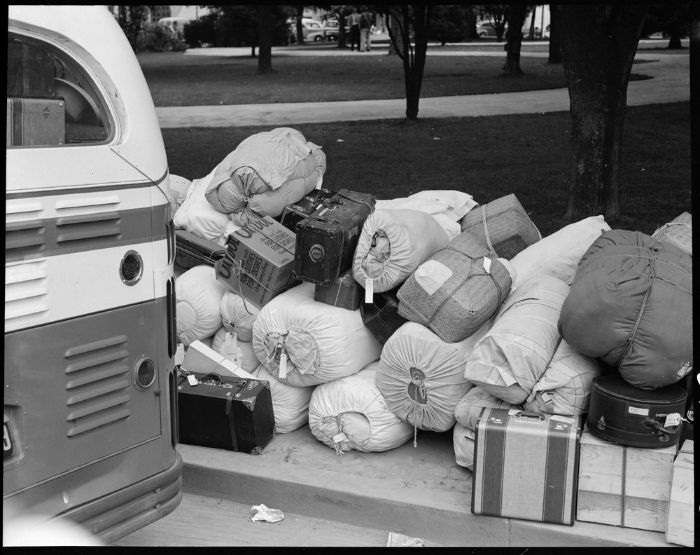Hayward, California. Baggage of evacuees of Japanese ancestry stacked at public park as evacuation bus prepares to leave for Tanforan assembly center. Evacuees will be transferred later to War Relocation Authority centers where they will spend the duration.