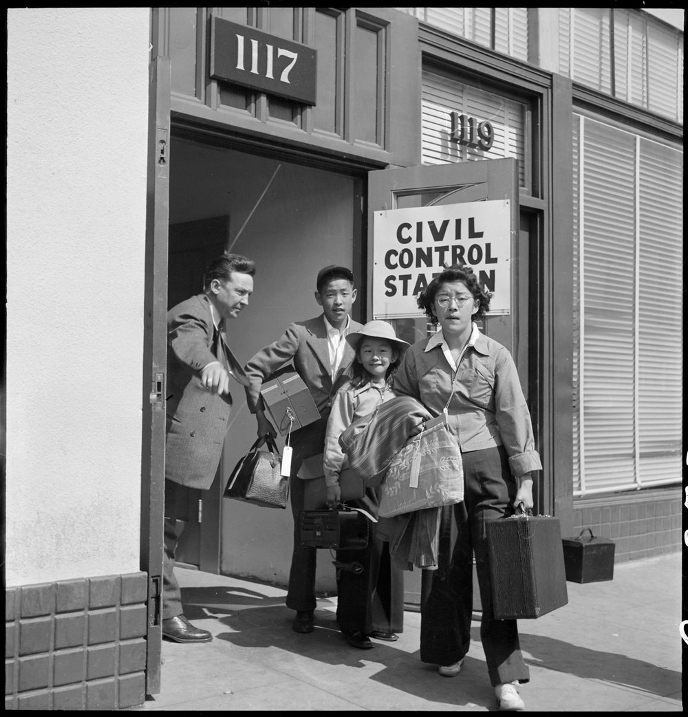 Oakland, California. Part of family unit of Japanese ancestry leave Wartime Civil Control Administration station on afternoon of evacuation, under Civilian Exclusion Order Number 28. Social worker directs these evacuees to the waiting bus.