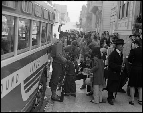 San Francisco, California. The Japanese quarter of San Francisco on the first day of evacuation from this area. About 660 merchants, shop-keepers, tradespeople, professional people left their homes on this morning for the Civil Control Station, from which they were dispatched by bus to the Tanforan Assembly center. This photograph shows a family about to get on a bus. The little boy in the new cowboy hat is having his identification tag checked by an official before boarding.