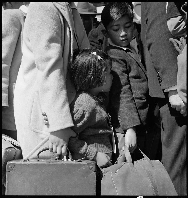 PRINT AVAILABLE May 2, 1942 — Byron, California. Third generation of American children of Japanese ancestry in crowd awaiting the arrival of the next bus which will take them from their homes to the Assembly center.