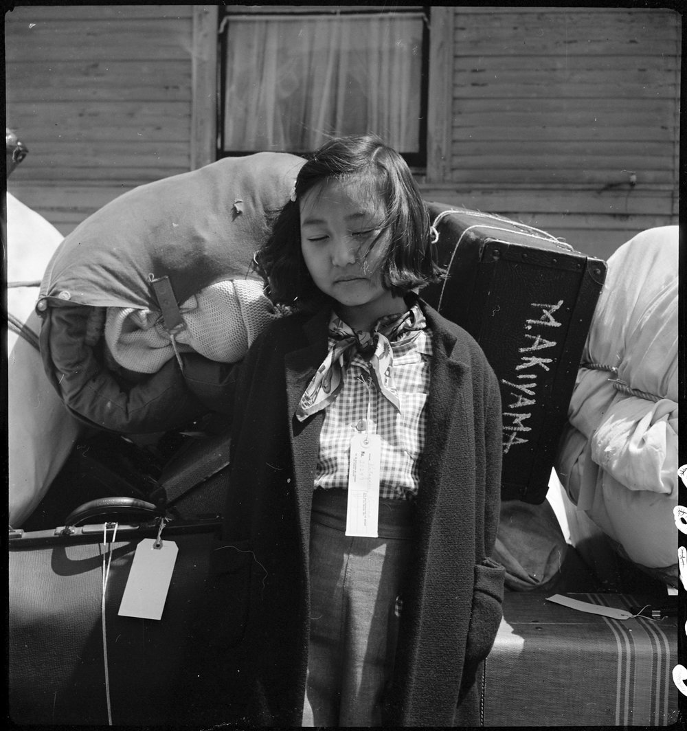 PRINT AVAILABLE May 6, 1942 — Oakland, California. Kimiko Kitagaki, young evacuee guarding the family baggage prior to departure by bus in one half hour to Tanforan Assembly center. Her father was, until evacuation, in the cleaning and dyeing business.