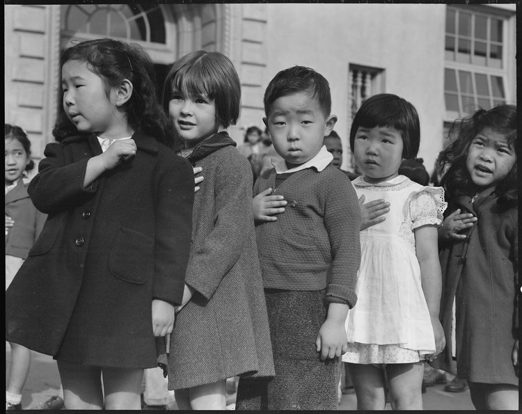 April 20, 1942 — San Francisco, California. Many children of Japanese ancestry attended Raphael Weill public School, Geary and Buchanan Streets, prior to evacuation. This scene shows first- graders during flag pledge ceremony. Evacuees of Japanese ancestry will be housed in War Relocation Authority centers for the duration. Provision will be effected for the continuance of education.