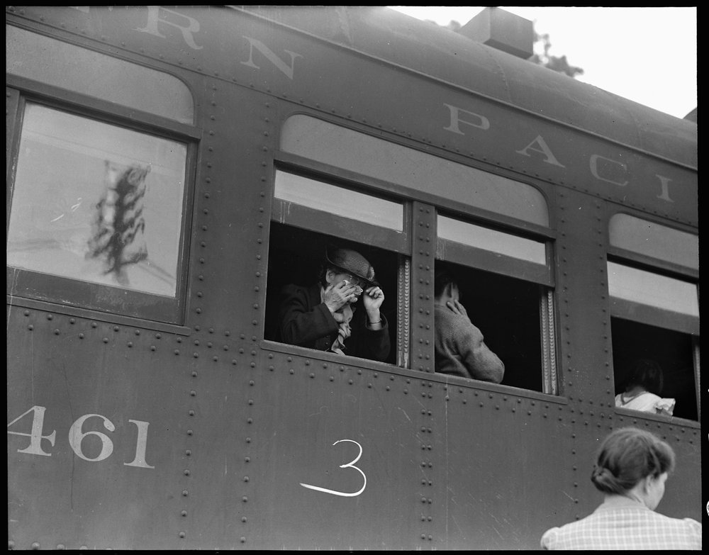 May 20, 1942 — Woodland, Yolo County, California. Ten cars of evacuees of Japanese ancestry are now aboard and the doors are closed. Their Caucasian friends and the staff of the Wartime Civil Control Administration stations are watching the departure from the platform. Evacuees are leaving their homes and ranches, in a rich agricultural district, bound for Merced Assembly Center about 125 miles away.