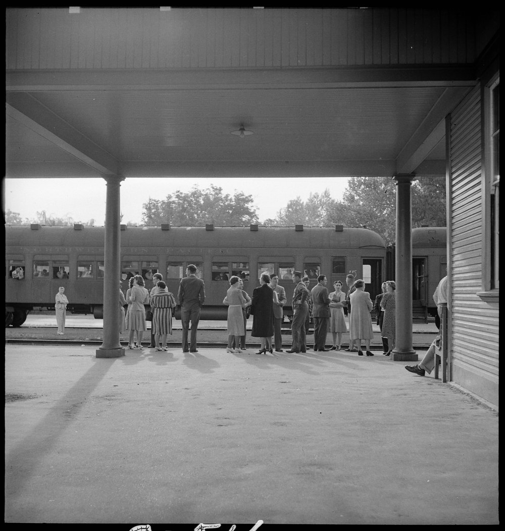 May 20, 1942 — Woodland, California. This staff of Wartime Civil Control Administration workers have completed their job and stand on the platform awaiting the departure of the special train which has been loaded with evacuees of Japanese ancestry bound for the Merced Assembly center, 125 miles away.