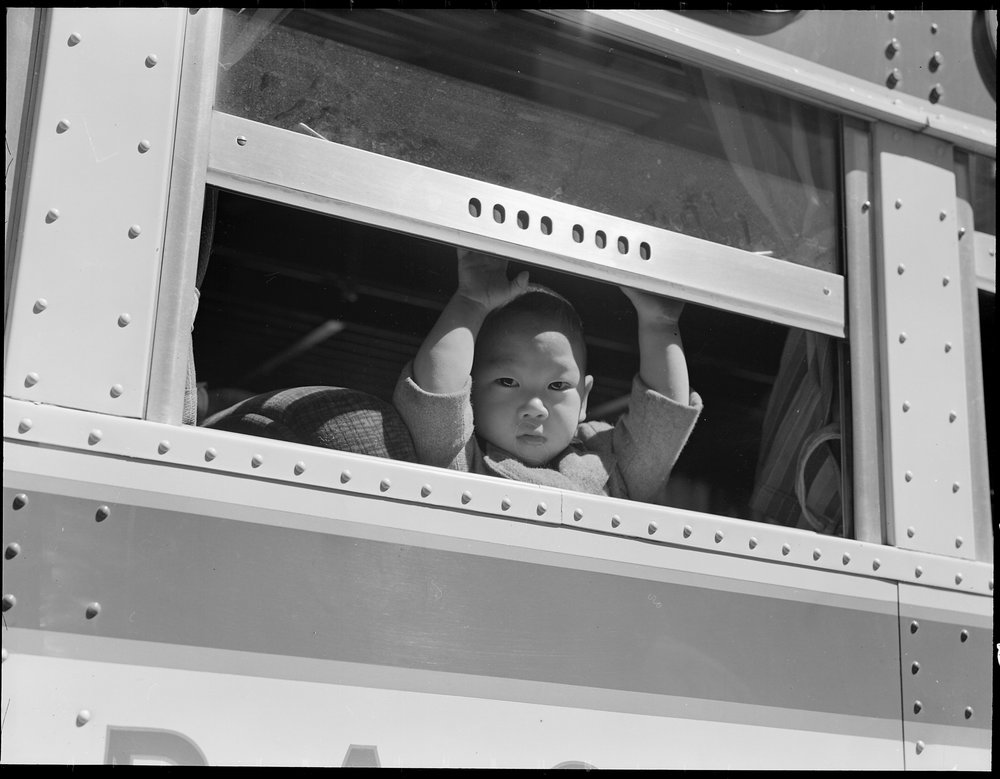April 29, 1942 — San Francisco, California. A young evacuee looks out the window of bus before it starts for Tanforan Assembly center. Evacuees will be transferred to War Relocation Authority centers for the duration.