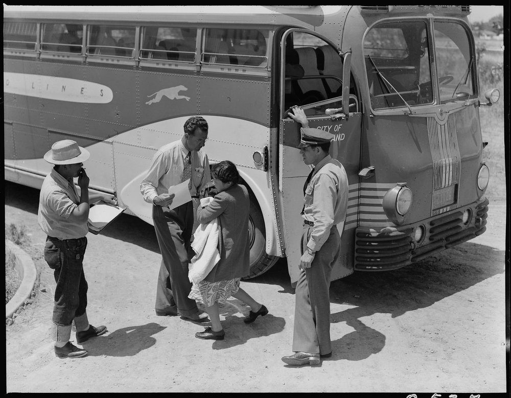 May 19, 1942 — Stockton, California. Young mother of Japanese ancestry has just arrived at this Assembly center with her baby and she is the last to leave the bus. Her identification number is being checked and she will then be directed to her place in the barracks after preliminary medical examination.