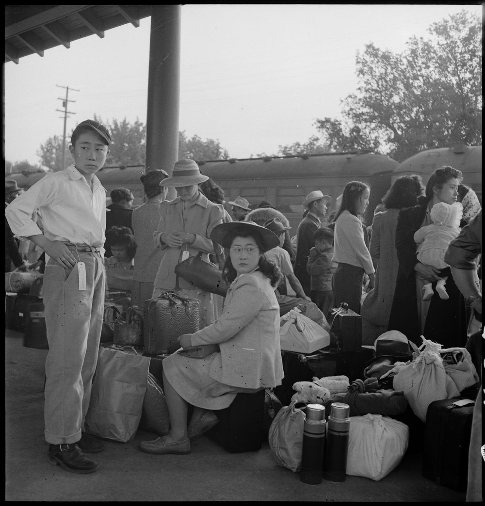 May 20, 1942 — Woodland, California. Families of Japanese ancestry with their baggage at railroad station awaiting the arrival of special train which will take them to the Merced Assembly center, 125 miles away.